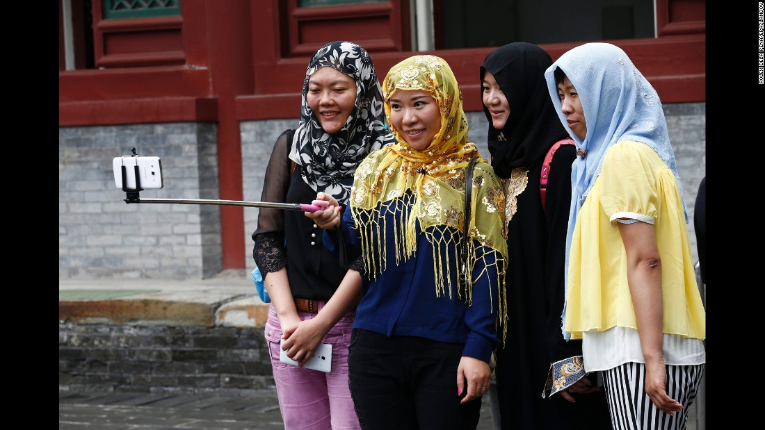Women take a selfie outside a mosque in Beijing after morning prayers on Saturday, July 18.