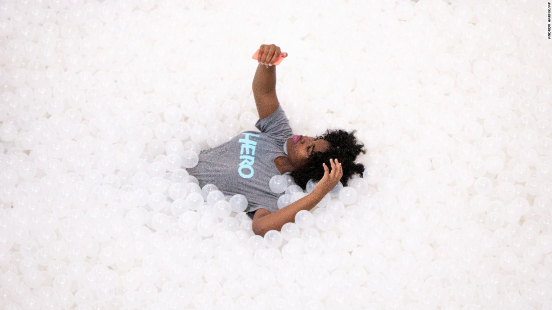 "A visitor takes a selfie while lying in a sea of plastic balls Friday, July 17, at ""The Beach,"" an interactive installation at the National Building Museum in Washington."