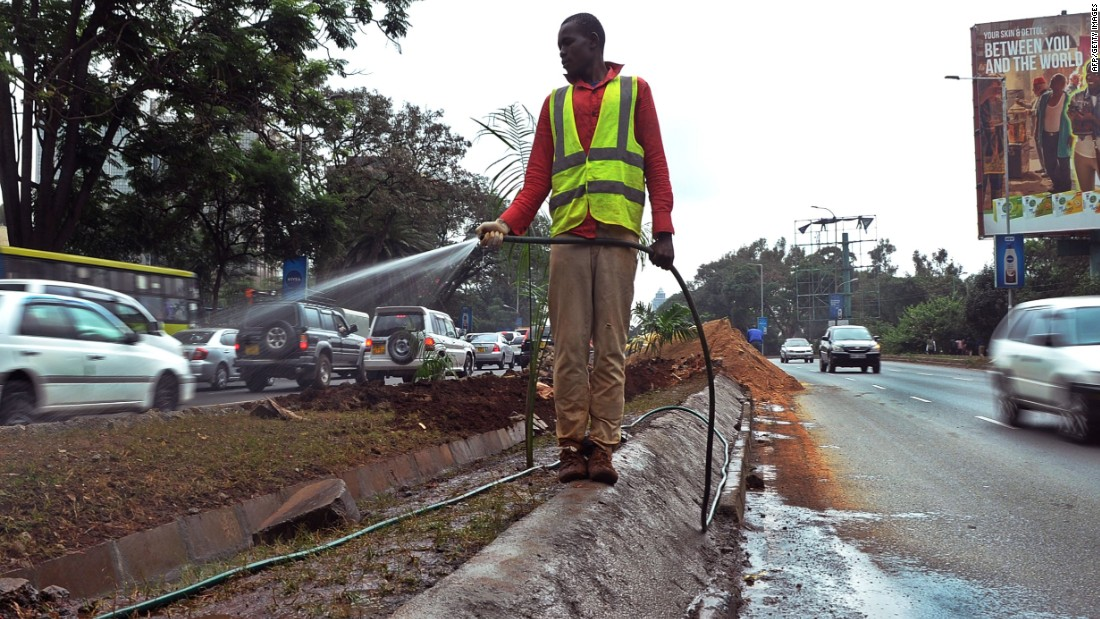 A worker waters new grass planted on a kerb along a street in Nairobi on July 9. before