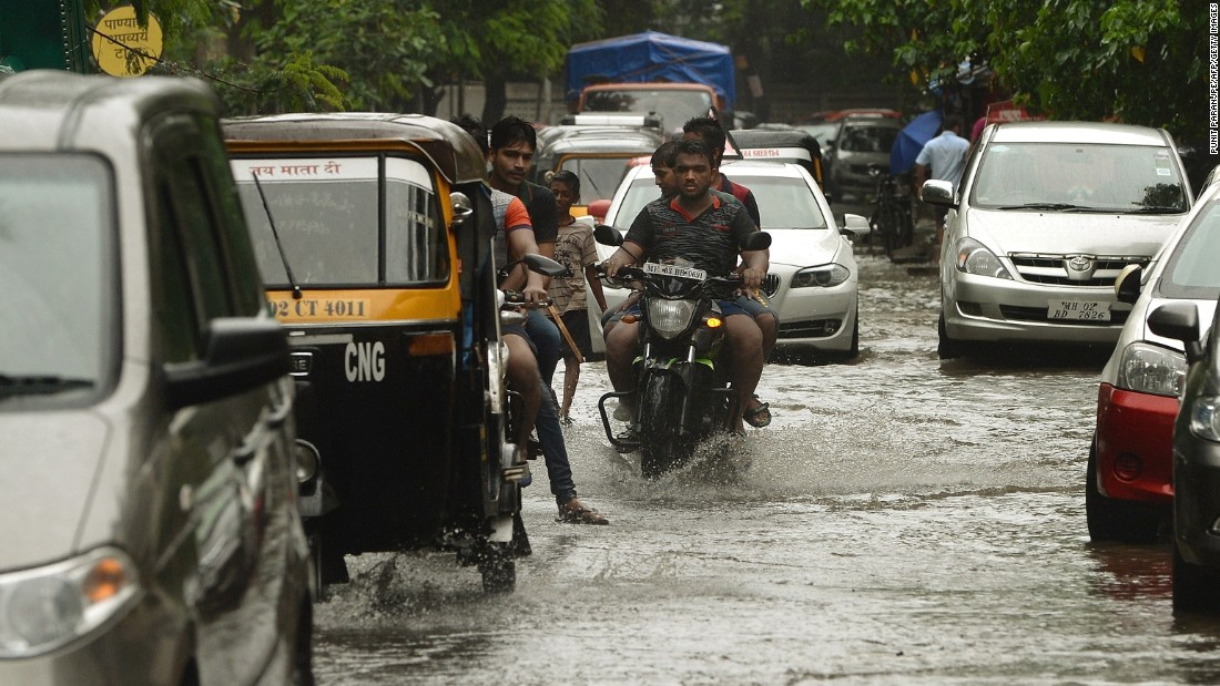 Commuters travel along a flooded street following heavy rain showers in Mumbai, India, on July 21.