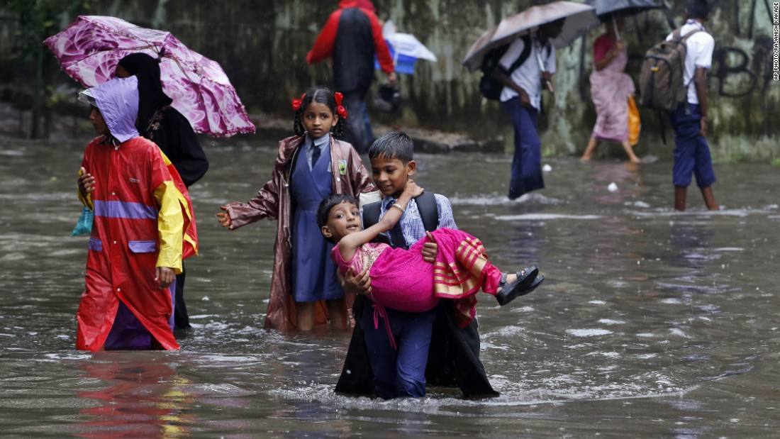 An Indian boy carries his sister and wades through a waterlogged street on his way to school in Mumbai, India, on July 21. Heavy rainfall -- leading to waterlogging in low-lying areas, disrupted local train services and traffic havoc -- threw normal life out of gear in the city on July 21.