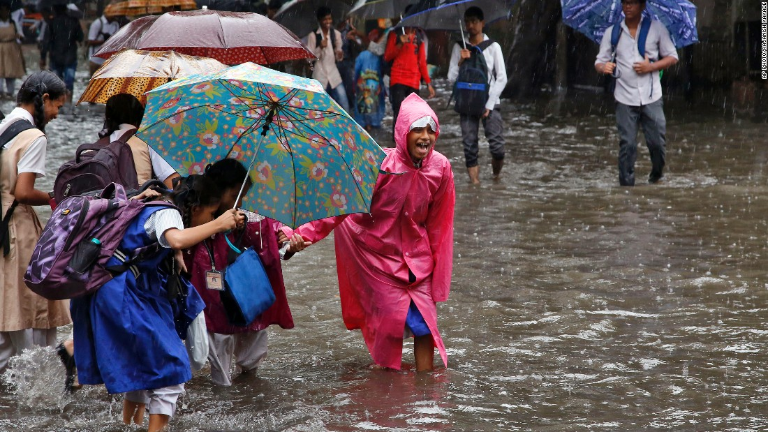 School children hold hands as they walk through a waterlogged street in Mumbai, India, on July 21.