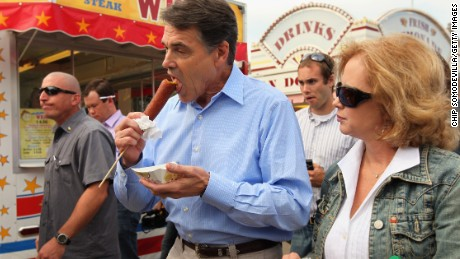 Republican presidential candidate and Texas Governor Rick Perry eats a 'veggie' corn dog and walks with his wife Anita while visiting the Iowa State Fair August 15, 2011 in Des Moines, Iowa.