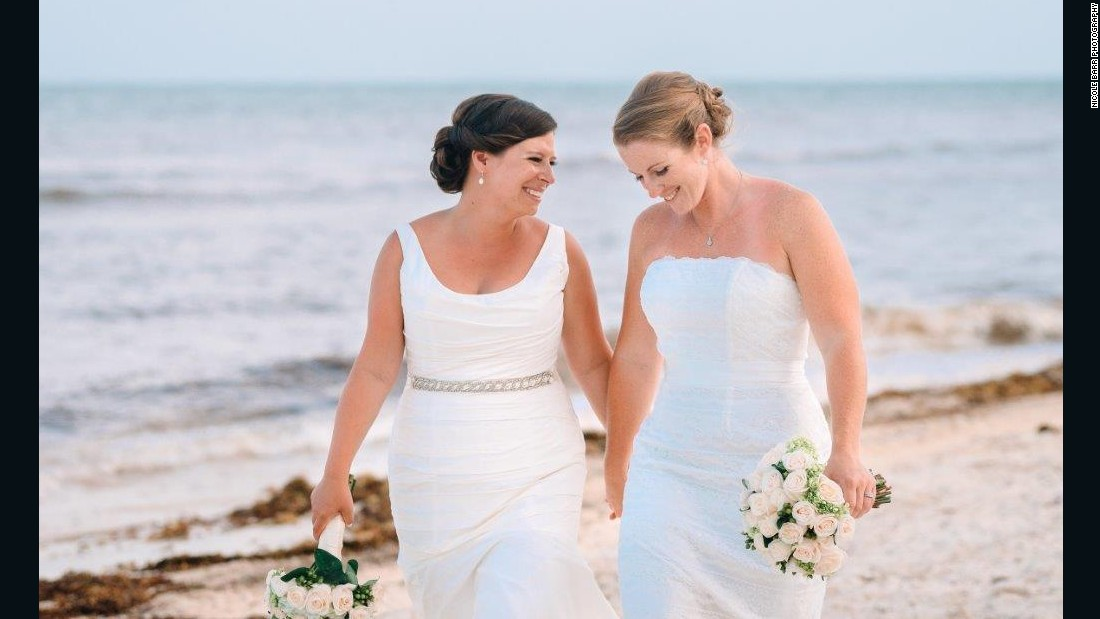 "Long Beach, New York, couple Lauren, left, and Christine Rapkin smile on their wedding day June 25, 2015, in Puerto Morelos, Mexico. They have been together for eight years and wed the day before the landmark Supreme Court decision. Christine is a critical care nurse and Lauren is an event planner and together they enjoy kayaking, beach volleyball and hiking with their dog. Photo courtesy<a href=""http://nicolebarrphotography.com/"" target=""_blank""> Nicole Barr Photography.</a>"