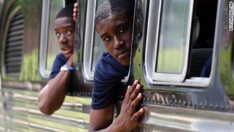 Tamir Brooks, right, and Sami Wylie look out the windows of the 1947 vintage bus their team traveled on this summer.
