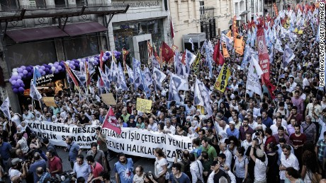 "Protesters hold flags and a banner reading ""Islamic state gangs will lose, our resisting people will win"" during a demonstration on July 20, 2015 in Istanbul, after a suicide bombing in the Turkish town of Suruc near the border with Syria killed at least 31."
