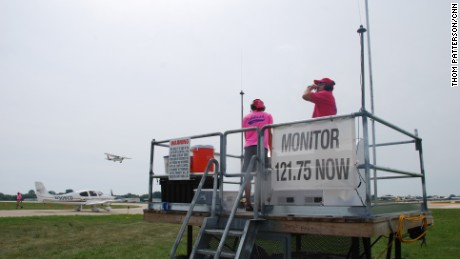 Air traffic controllers use special mobile platforms to direct airplane departures from the center of the Oshkosh airfield.