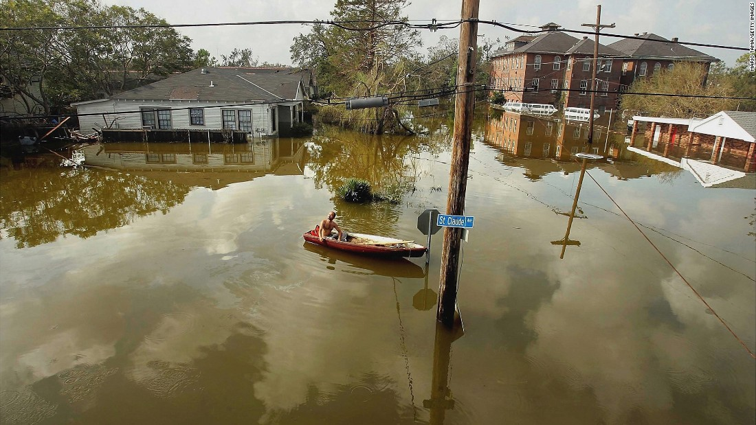 A man in New Orleans' Lower Ninth Ward rides a canoe in high water on August 31, 2005. Hurricane Katrina struck the Gulf Coast on August 29, 2005. After levees and flood walls protecting New Orleans failed, much of the city was underwater. At least 1,833 died in the hurricane and subsequent floods. It was the costliest natural disaster in U.S. history.