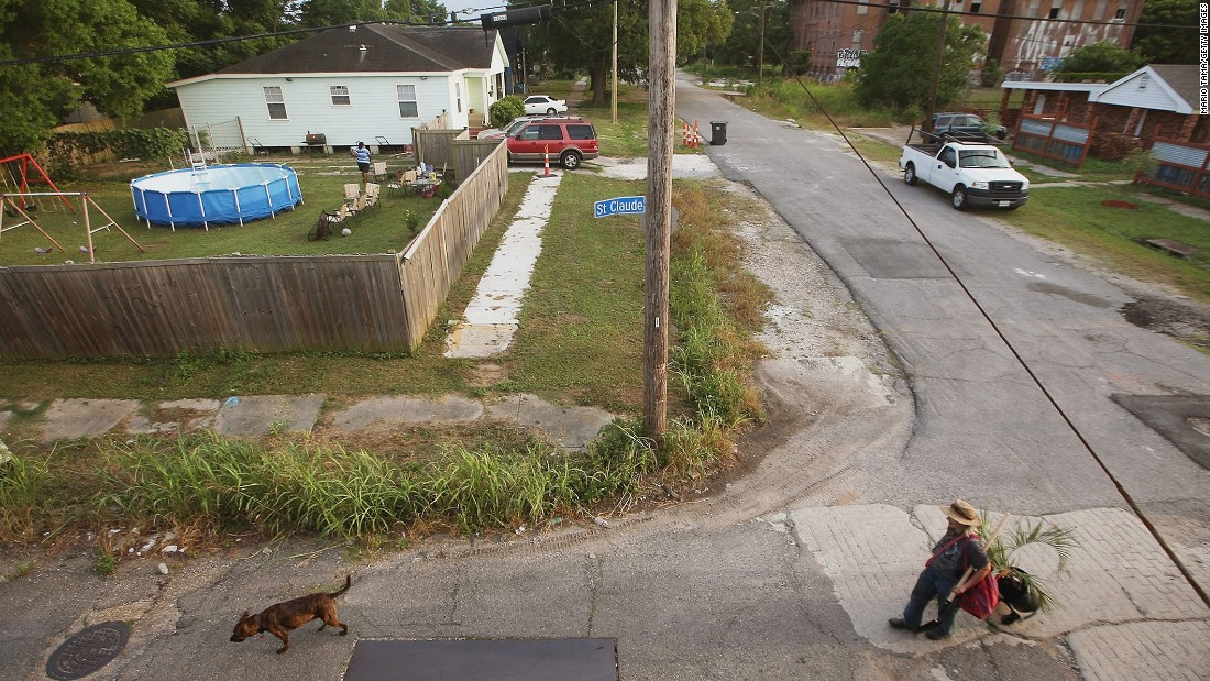 A woman walks with a dog in the Lower Ninth Ward on May 16, 2015.
