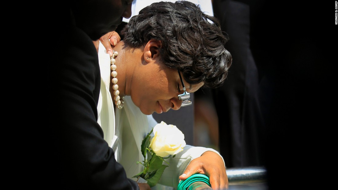 Sandra Bland's sister, Sharon Cooper, kneels at Bland's burial site on July 25.