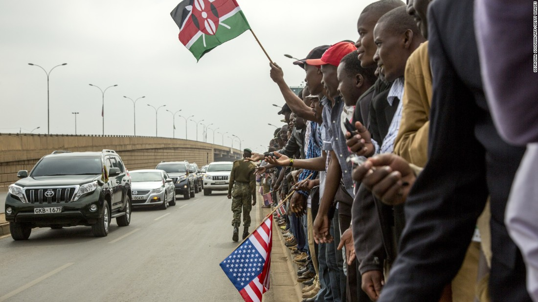 Kenyans wave to members of Kenya's Parliament as they wait for Obama's arrival on July 26.