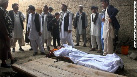 Afghan residents and relatives stands over the bodies of victims after a gunfight broke out at a wedding party at Deh Salah district of Baghlan Province killing 21 people.