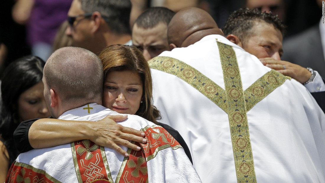 Dondie LeBlanc Breaux, left, and Kevin Breaux, parents of Mayci Breaux, are hugged by clergy outside the church.