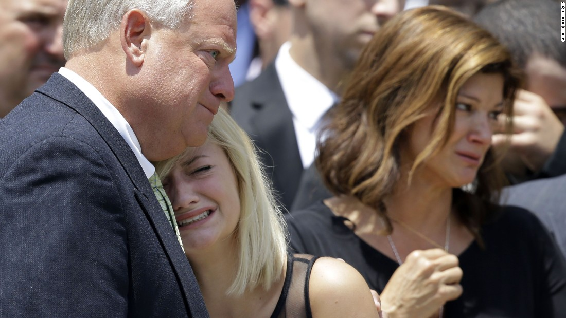 Ali Breaux, center, sister of Mayci Breaux, is comforted outside of the church.
