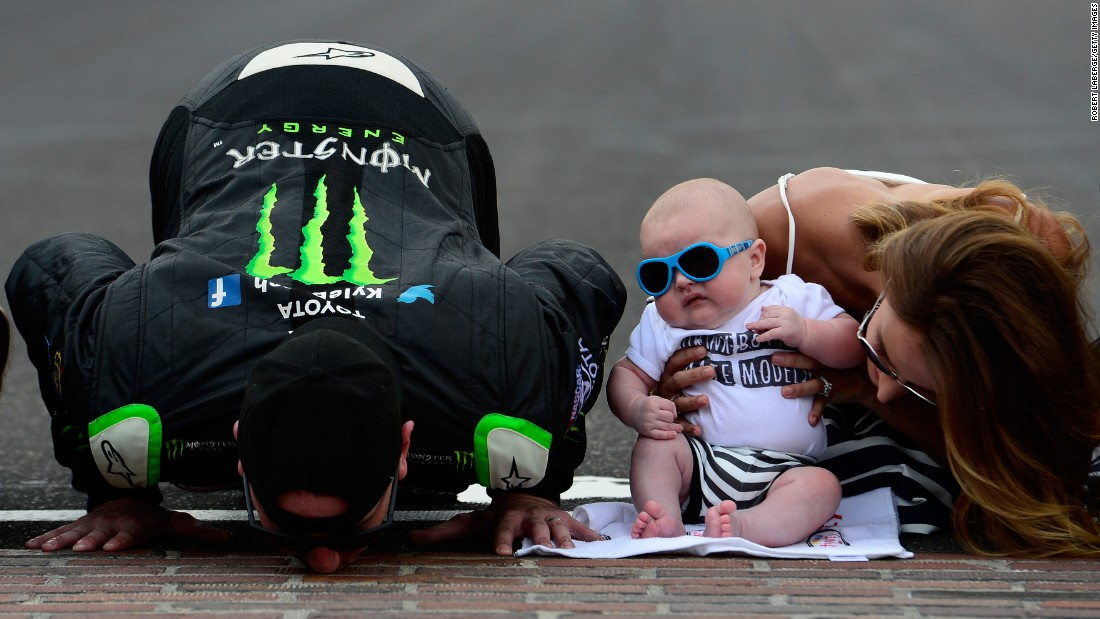 NASCAR driver Kyle Busch kisses the bricks at Indianapolis Motor Speedway after winning the Xfinity Series race there on Saturday, July 25. He was joined by his wife, Samantha, and their son, Brexton. Busch also won the Sprint Cup race on Sunday -- his third Sprint Cup victory in a row.