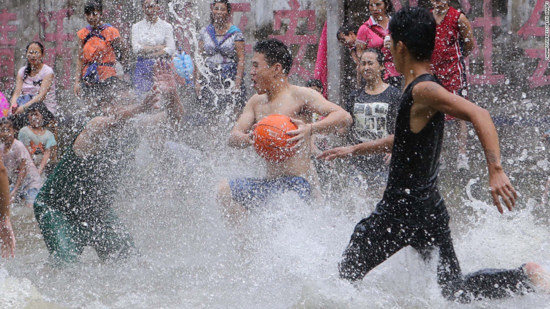 "Villagers in Beijing play basketball on a court filled with spring water to celebrate the Xinhe Festival on Thursday, July 23. ""Xinhe"" means newly planted crops, and the festival is an annual tradition to pray for harvests."