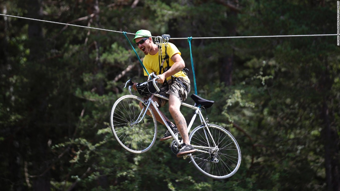 A fan rides a bicycle as he is suspended from a cable during the 17th stage of the Tour de France on Wednesday, July 22.