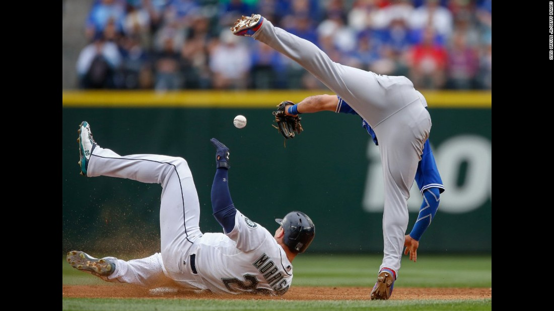 Seattle's Logan Morrison, left, steals second base as Toronto's Devon Travis falls over him on Saturday, July 25.