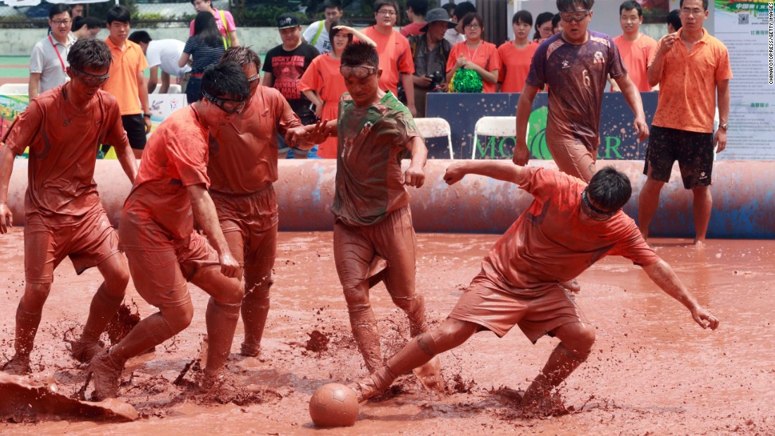 Players compete for the ball during a game of swamp soccer in Beijing on Friday, July 24.