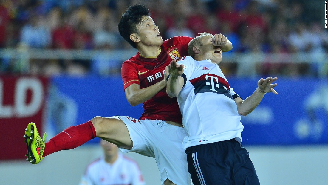 Zou Zheng, a soccer player with Chinese club Guangzhou Evergrande, tussels with Bayern Munich's Sebastian Rode, right, during an exhibition match in Guangzhou, China, on Thursday, July 23.