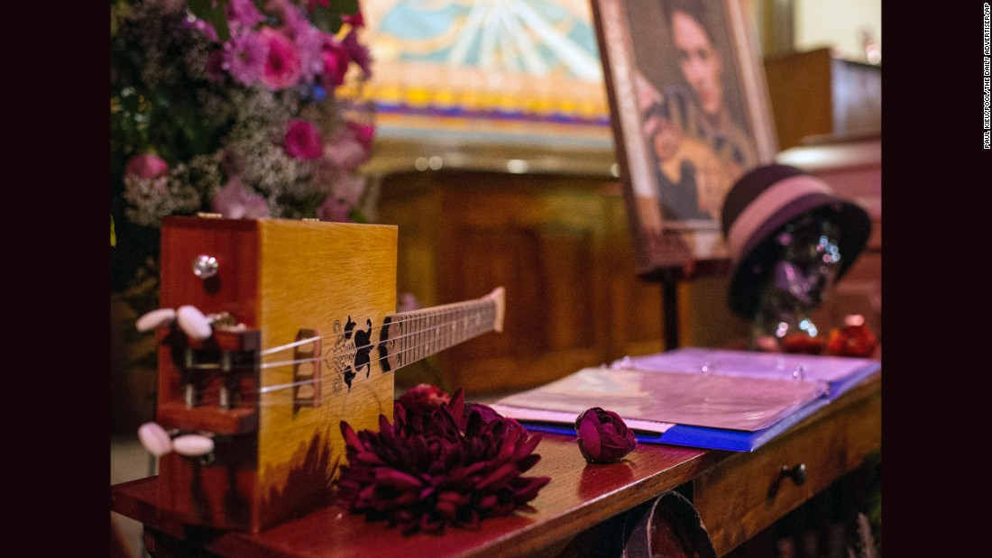 A string instrument and song book are displayed next to the casket of Jillian Johnson.