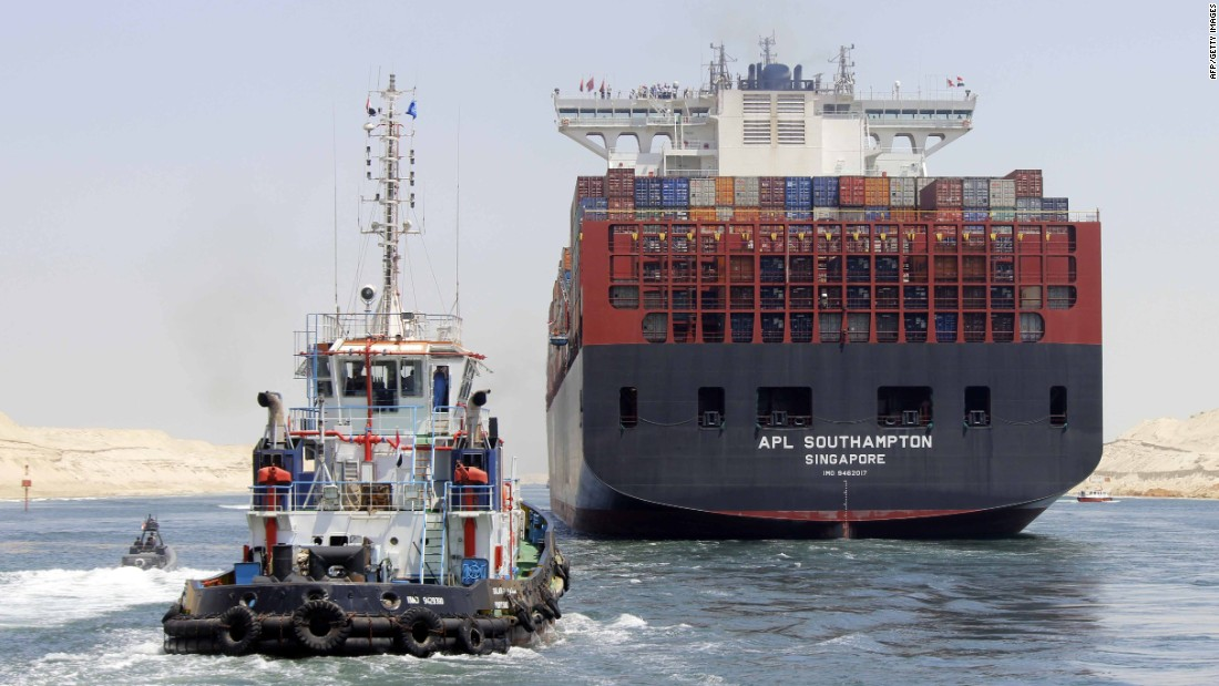 "Boats, including a container ship, cross the new waterway of the Suez Canal on July 25, 2015, in the Egyptian port city of Ismailia, east of Cairo. Egypt started the first trial run of its ""new Suez canal,"" officials said, ahead of the new shipping route's formal inauguration on August 6, 2015 -- a year after construction began."