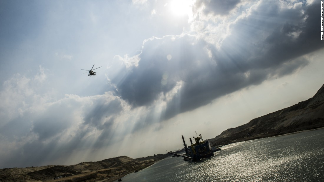 An Egyptian army helicopter flies over a dredger at work on the new waterway of the Suez Canal on June 13, 2015, in the port city of Ismailia, east of Cairo. The government hopes the ambitious industrial project will generate $100 billion in revenue and create 1 million jobs.