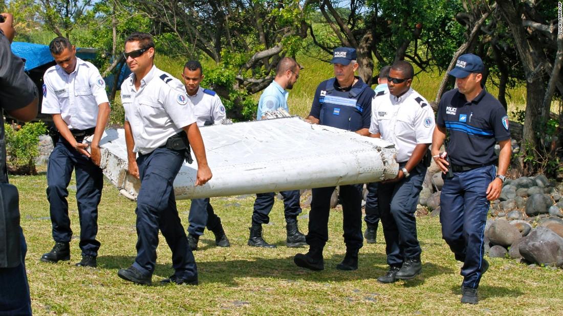 Police carry debris on July 29.