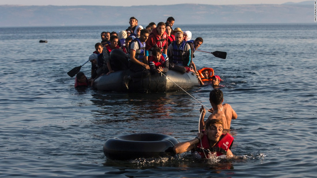 Two migrants pull a dinghy filled with Syrian and Afghan refugees as they arrive on the Greek island of Lesbos on Monday, July 27. Tens of thousands of migrants have arrived in Greece so far this year, overwhelming local authorities, aid groups say.