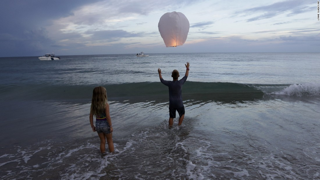 "Andrew Grubowski, 10, releases a lantern in Stuart, Florida, during a vigil for Austin Stephanos and Perry Cohen on Tuesday, July 28. The two teenagers <a href=""http://www.cnn.com/2015/07/28/us/florida-missing-teens-boat/"" target=""_blank"">have been missing</a> since July 24, when they went out on a boat to go fishing. The boat was found capsized off the Florida coast on July 26."