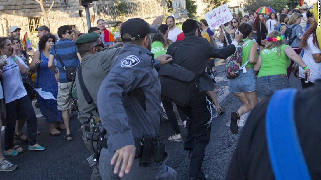 Security forces reach for a knife-wielding Schlissel.