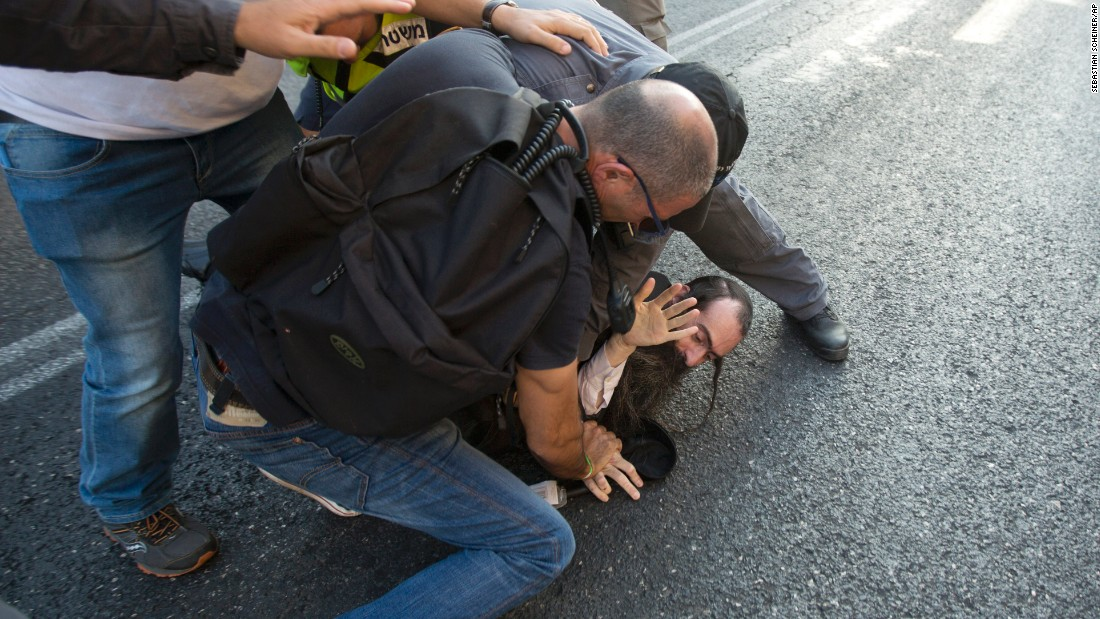 Police wrestle Schlissel to the ground and arrest him.