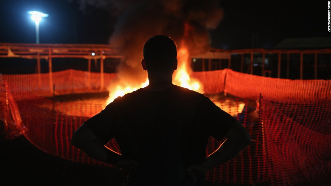 Doctors Without Borders staffer Alex Eilert Paulsen watches as mattresses and bed frames burn at the Ebola Treatment Unit in Paynesville, Liberia, on January 31. The organization reduced its number of beds from 250 to 30 as gains were made in battling the virus.