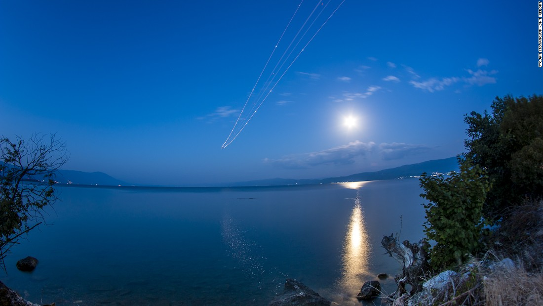 "<a href=""http://ireport.cnn.com/docs/DOC-1261121"">Stojan Stojanovski</a> was near the Ohrid ""St. Paul the Apostle"" Airport to photograph the blue moon.  ""The moon was very bright,"" he said. He waited for planes to take off from the airport to get this long exposure shot."