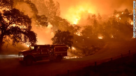Caption:A Cal Fire truck is driven away from flames as the Rocky fire burns near Clear Lake, California on August 2, 2015. The fire has charred more than 27,000 acres, and is currently only 5% contained. AFP PHOTO/JOSH EDELSON (Photo credit should read Josh Edelson/AFP/Getty Images)