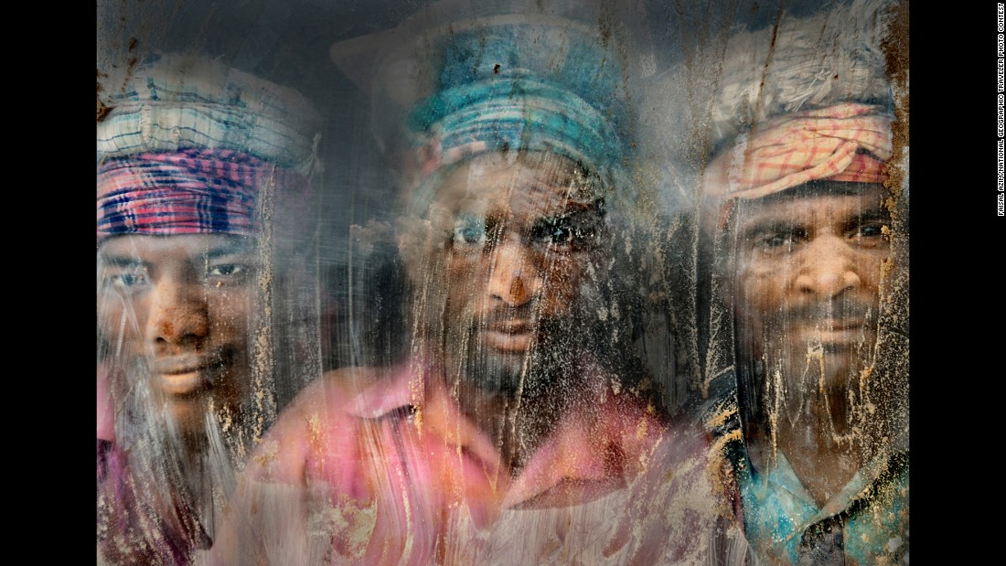 """(This) gravel-crush working place remains full of dust and sand,"" Azim said of this photo from Chittagong, Bangladesh. ""Three gravel workmen are looking through the window glass at their working place."""