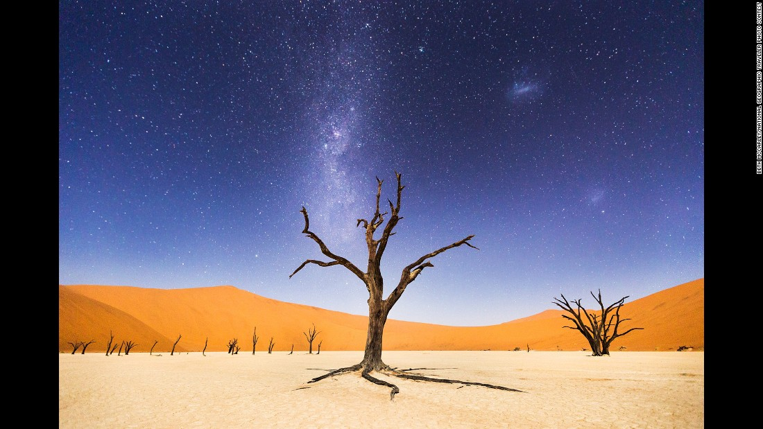 """The night before returning to Windhoek, we spent several hours at Deadvlei"" in Namibia, McCarley said. ""The moon was bright enough to illuminate the sand dunes in the distance, but the skies were still dark enough to clearly see the Milky Way and Magellanic Clouds. Deadvlei means 'dead marsh.' The camelthorn trees are believed to be about 900 years old but have not decomposed because the environment is so dry."""