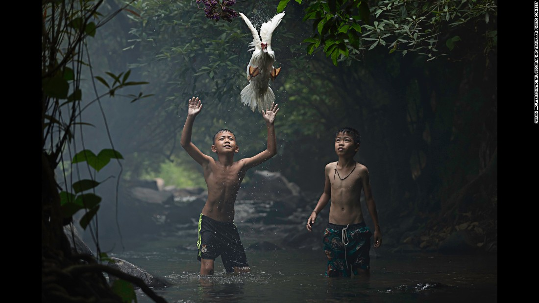 """Two boys are trying to catch a duck at the stream of the waterfall (in) Nong Khai Province, Thailand,"" Wouters said."
