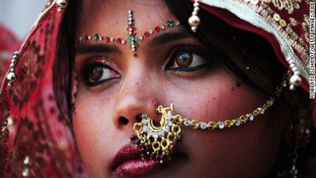 An Indian bride looks on as she and ten other women waiting to marry wait for their grooms to arrive at their wedding ceremony at a local Hindu temple in New Delhi on March 3, 2014. Eleven couples tied the knot at the same time. AFP PHOTO/Roberto SCHMIDT (Photo credit should read ROBERTO SCHMIDT/AFP/Getty Images)