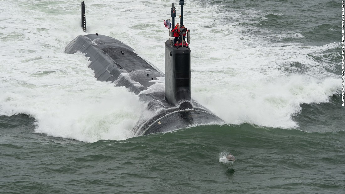 "A dolphin swims in front of the Virginia-class attack submarine USS John Warner during its sea trials in May 2015. Virginia-class subs, displacing 7,800 tons and at 377 feet long, ""are designed to seek and destroy enemy submarines and surface ships; project power ashore with Tomahawk cruise missiles and special operation forces (SOF); carry out inntelligence, surveillance, and reconnaissance (ISR) missions; support battle group operations; and engage in mine warfare,"" according to the Navy."