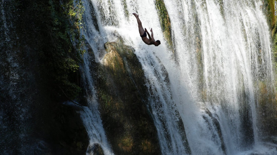 A competitor dives from a waterfall during a contest held in Jajce, Bosnia-Herzegovina, on Saturday, August 1.