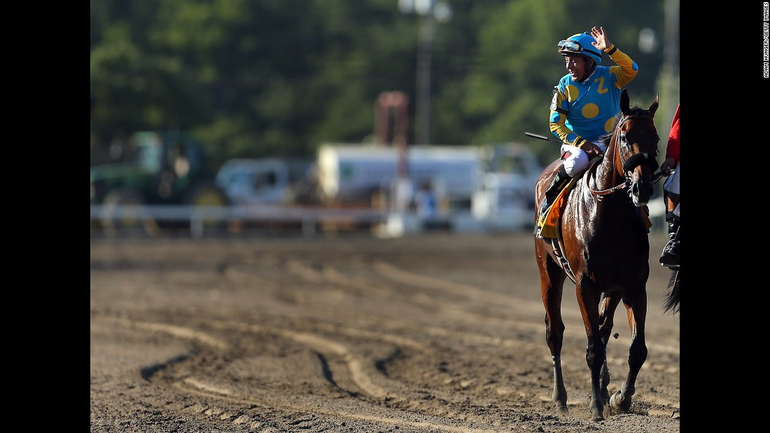 Victor Espinoza, aboard Triple Crown winner American Pharoah, waves after yet another victory -- this one the William Hill Haskell Invitational in Monmouth, New Jersey, on Sunday, August 2. It was Pharoah's eighth straight win.