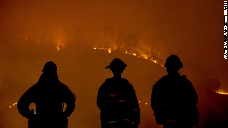 CLEARLAKE, CA - AUGUST 02:  Cal Fire firefighters look on as the Rocky Fire burns through trees on August 2, 2015 near Clearlake, California. Over 1,900 firefighters are battling the Rocky Fire that burned over 22,000 acres since it started on Wednesday afternoon. The fire is currently five percent contained and has destroyed at least 14 homes.  (Photo by Justin Sullivan/Getty Images)