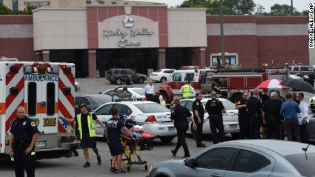 Dozens of law enforcement and emergency responders work in the parking lot after a suspect wielding a hatchet and gun inside a Nashville-area movie theater died after exchanging gunshots with SWAT team members that stormed the theater, police said, Wednesday, Aug. 5, 2015. The suspect, who was not identified, was armed with a gun and hatchet at the Carmike Hickory 8 theater in Antioch, said Don Aaron, a spoke, man for Metro Nashville police. (AP Photo/Mark Zaleski)
