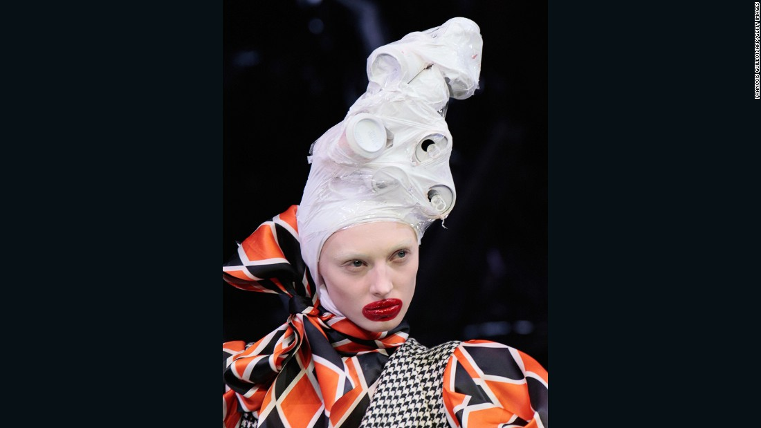 Models at Alexander McQueen's controversial Horn of Plenty collection -- which included a set littered with stylized trash and fabrics meant to look like garbage bags -- had white-washed faces, exaggerated lacquered lips and headpieces made from all sorts of trash.