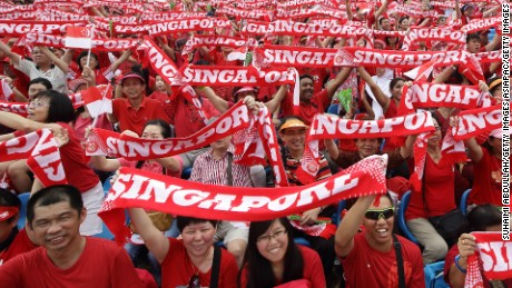 SINGAPORE - AUGUST 09:  People cheer during the National Day Parade at the Float at Marina Bay on August 9, 2014 in Singapore.  Singapore celebrates it's 49th birthday with a parade theme of 'Our People, Our Home'.  (Photo by Suhaimi Abdullah/Getty Images)