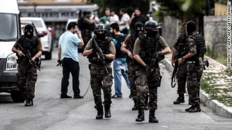 Turkish special force police officers take cover during clashes with attackers on August 10, 2015 at the Sultanbeyli district in Istanbul. Turkey's largest city Istanbul was Monday shaken by twin attacks on the US consulate and a police station as tensions spiral amid the government's air campaign against Kurdish militants.