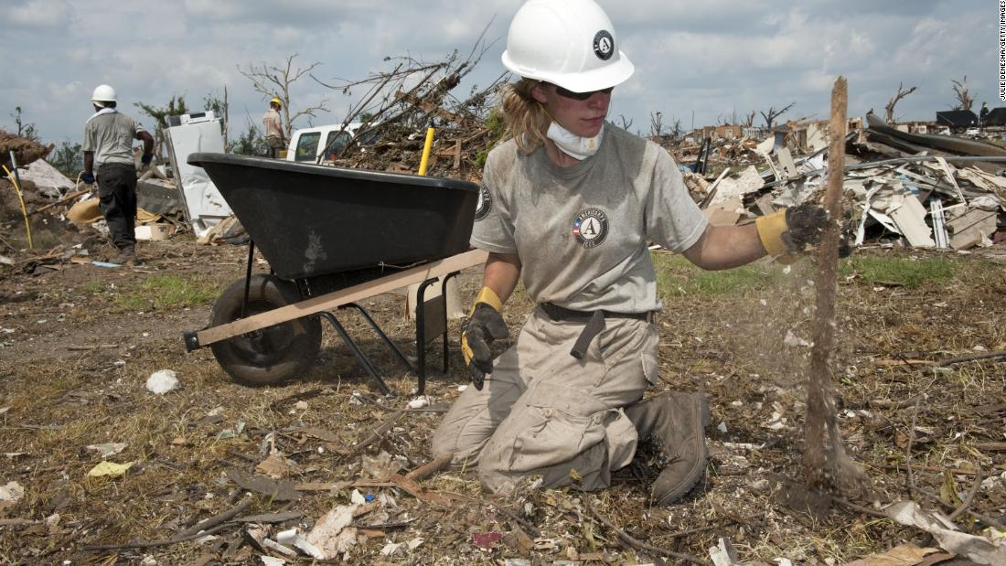 JOPLIN, MO- JUNE 18: AmeriCorps volunteer Teri Jacobs picks up wood and debris from the remains of a home on June 18, 2011, in Joplin, Missouri.  More than 28,000 volunteers have made their way to Joplin to help clear debris in the weeks following an EF5 tornado that leveled parts of the city.  (Photo by Julie Denesha/Getty Images)