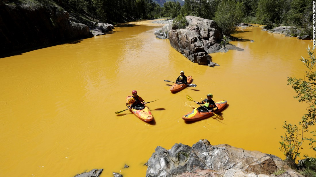 Kayakers float along the Animas River near Durango, Colorado, on August 6, in water colored from the mine waste spill.
