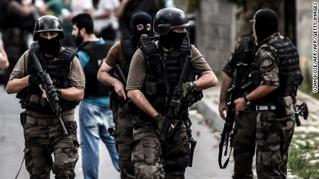 Turkish special force police officers take cover during clashes with attackers on August 10, 2015 at the Sultanbeyli district in Istanbul. Turkey's largest city Istanbul was Monday shaken by twin attacks on the US consulate and a police station as tensions spiral amid the government's air campaign against Kurdish militants. AFP PHOTO / OZAN KOSE        (Photo credit should read OZAN KOSE/AFP/Getty Images)